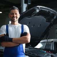 Mechanic near automobile in service center, space for text. Car diagnostic