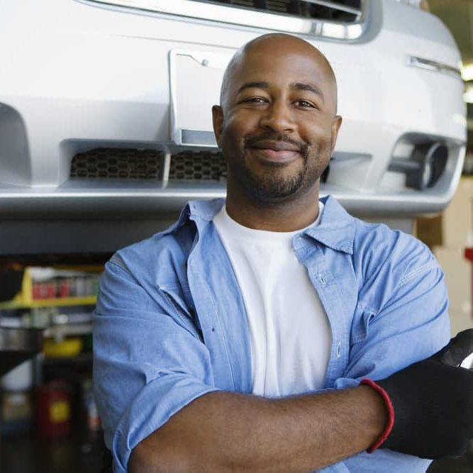 Confident Mechanic Holding Wrench At Garage